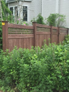Authentic walnut wood grain vinyl fence from grand illusion manufacture maintenance free looks like wood and blends beautiful with foliage  Rye NY
